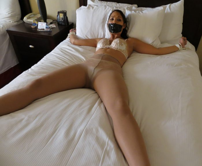Scared girl in tan tights tied to a bed.