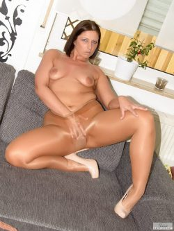 Brunette playing with her pussy in tan tights.