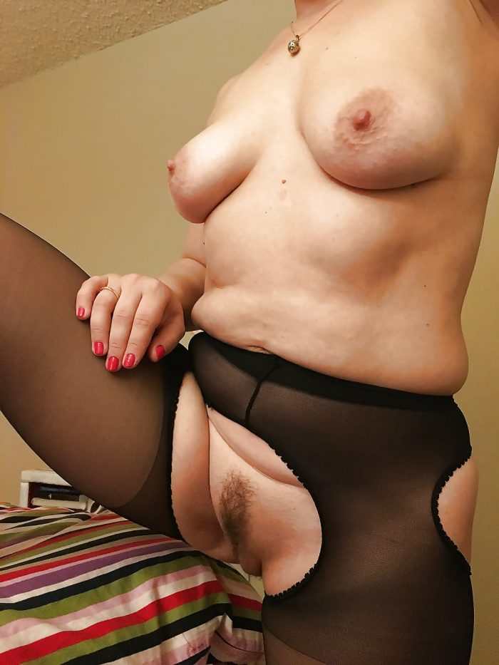Plump mature showing pussy under black suspender tights.