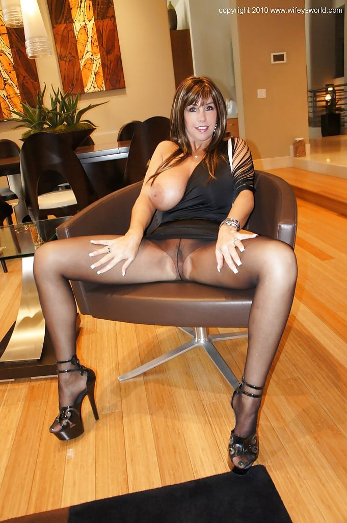 Stunning mature in black tights showing one tit and her pussy.