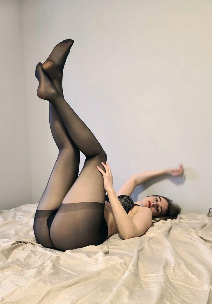 Black tights on a bed, no panties.